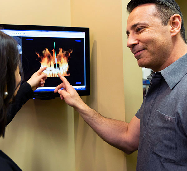 Doctor pointing to dental implants in xray on screen